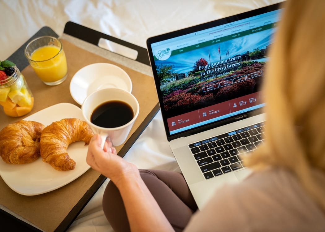 Woman working on laptop on hotel bed