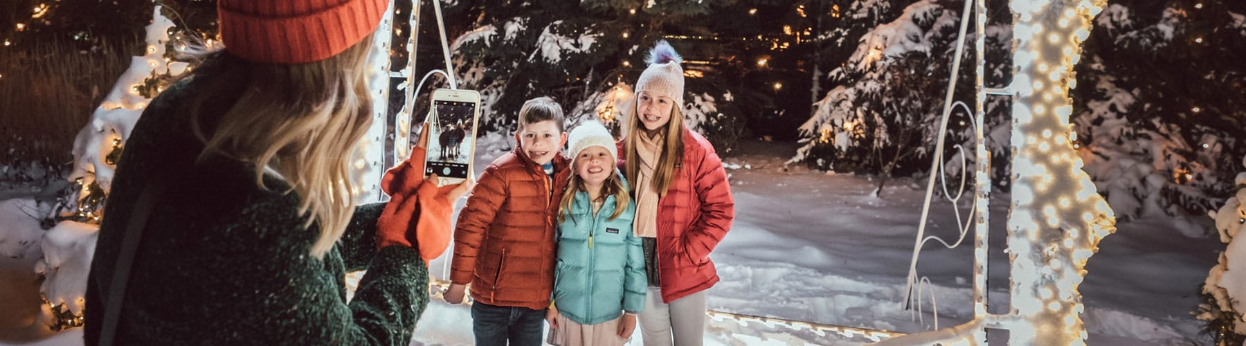 Family Photo Outside by Holiday Lights