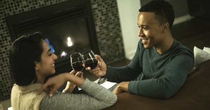 Couple in a villa drinking wine by the fire